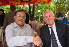 A photo of Ajay Sood and Arthur Carty shaking hands.